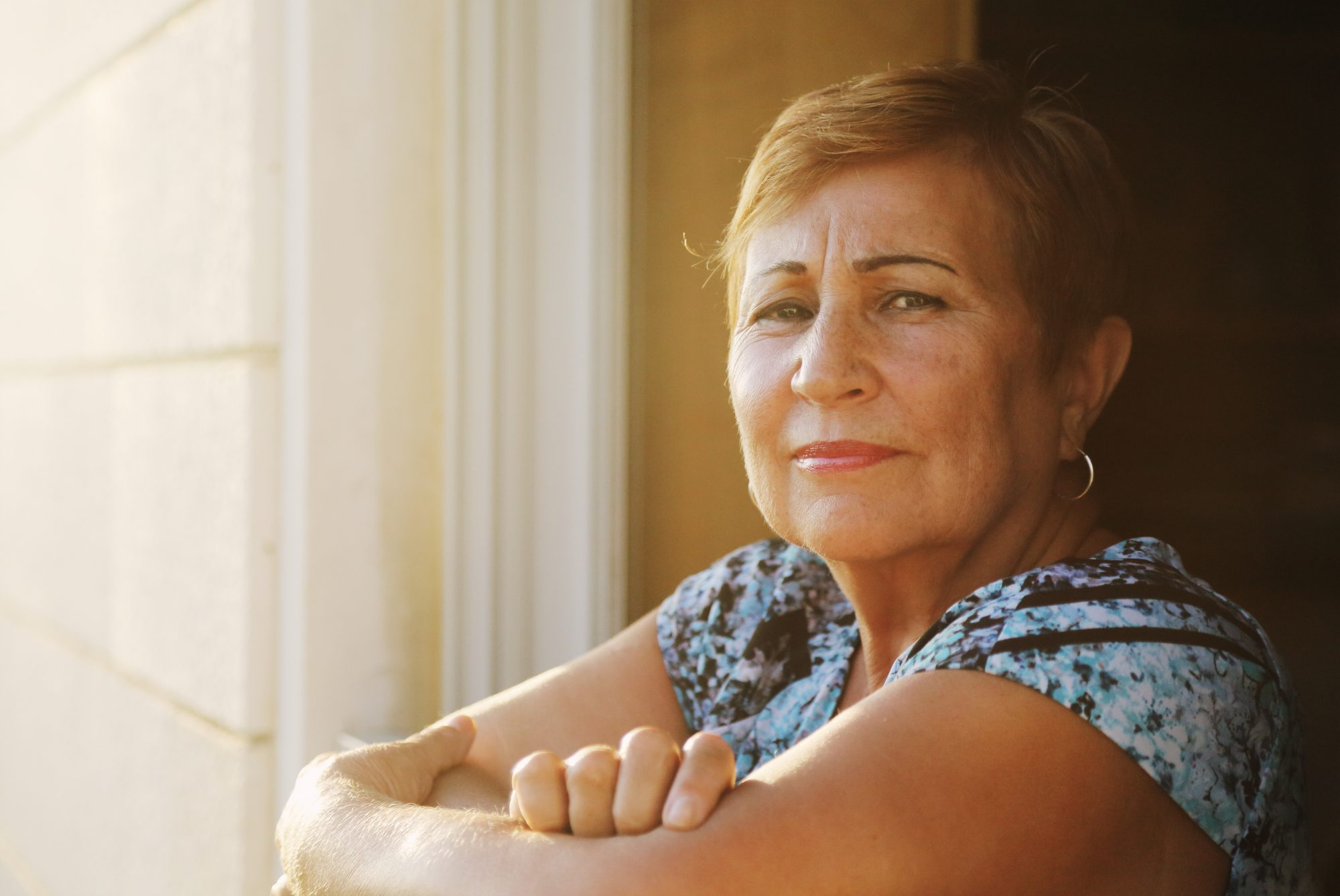 older latina woman looking out from her balcony