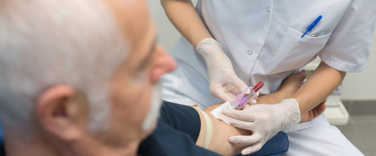 young female doctor taking senior patients blood sample